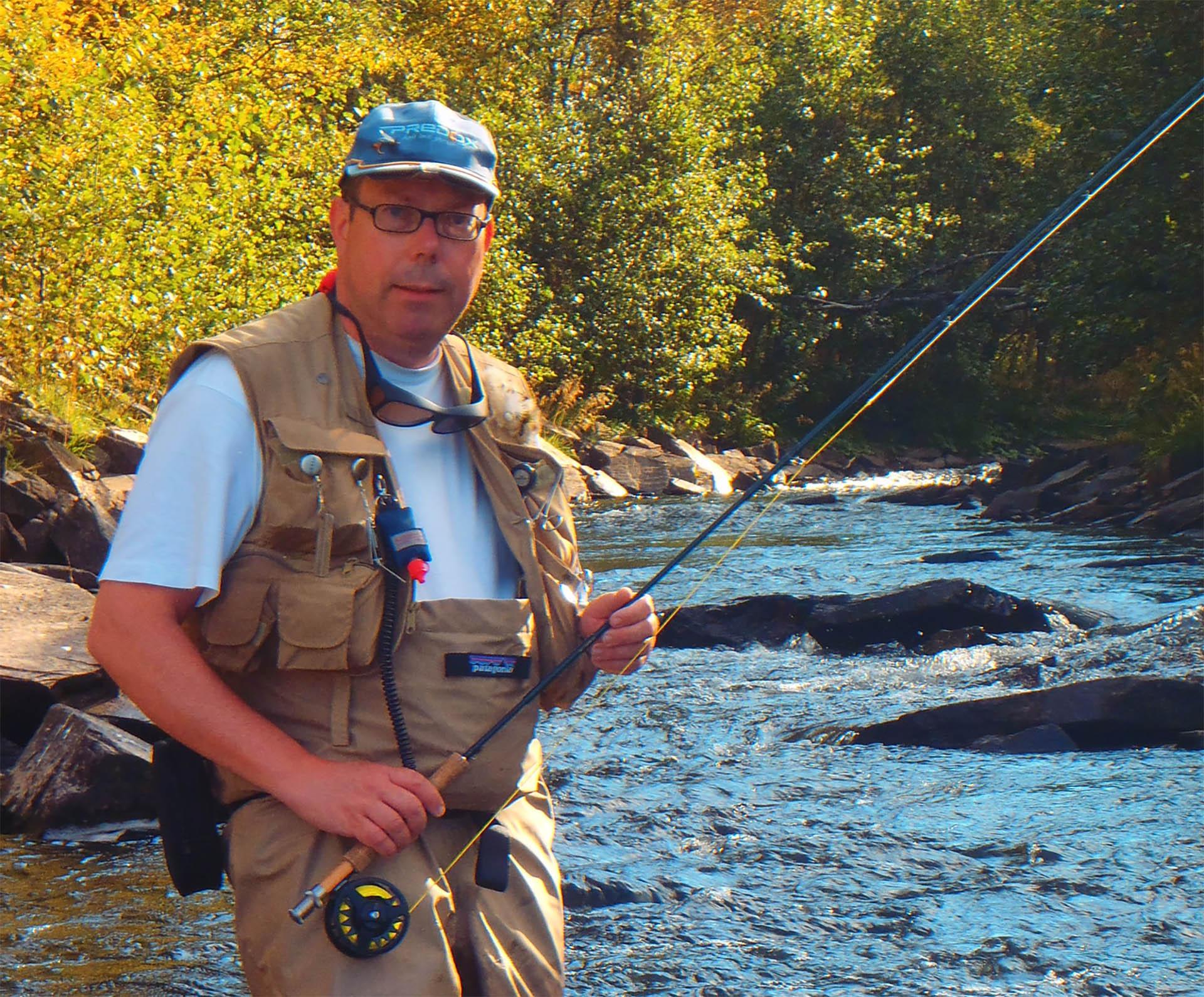 Visgids Paul met hengel in een rivier in Noorwegen